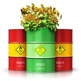 Green biofuel drum with sunflowers in front of red oil or gas ba. Creative abstract ecology, alternative sustainable energy and environment protection saving Royalty Free Stock Images