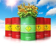 Green biofuel drum with sunflowers in front of red oil or gas ba. Creative abstract ecology, alternative sustainable energy and environment protection saving Stock Image