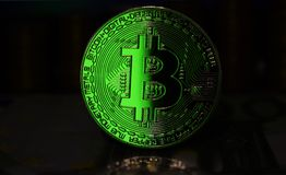 Green Bitcoin BTC coin is surrounded by a gloomy background royalty free stock images