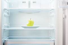 Green bitten apple on white plate in open empty refrigerator Stock Image