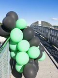 Green and black balloons. In a bridge Stock Images