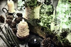 Green and black candles, luminous bottles with lights, moss and succulent on witch table. Magic gothic ritual. royalty free stock photography