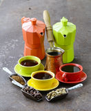 Green, black coffee beans and different utensils for boiling coffee Stock Image
