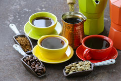 Green, black coffee beans and different utensils for boiling coffee Stock Images