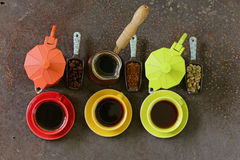 Green, black coffee beans and different utensils for boiling coffee Stock Photos