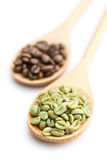 Green and black coffee beans in wooden spoon Stock Image