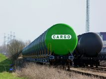 Green and black freight trains in rail yard under grey blurry sky royalty free stock images