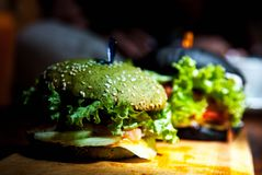 Green, black mini burgers with vegetables . royalty free stock image