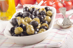 Green and black olive in a bowl Stock Photos