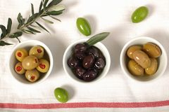 Three kind of olives and young olive branch on cloth napkin. Green and black olive in porcelain bowl with young olive twig on cloth napkin Stock Photos