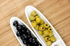 Green and black olives. On a white plates Stock Photo