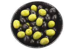 Green and black olives in black bowl. Close up, over white royalty free stock images