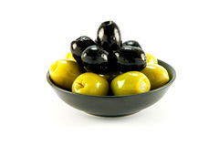Green and Black Olives in a Bowl. Green and black olives in a small black bowl on a white background Royalty Free Stock Image