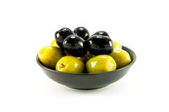 Green and Black Olives in a Bowl. Green and black olives in a small black bowl on a white background Royalty Free Stock Photo