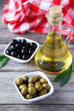 Green and black olives in bowl on grey wooden background. Royalty Free Stock Images