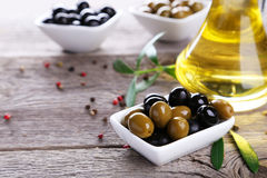 Green and black olives in bowl on grey wooden background. Stock Photos