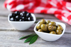 Green and black olives in bowl on grey wooden background. Royalty Free Stock Image