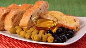Green and black olives, a bowl with olive oil and homemade bread. Stock Photo