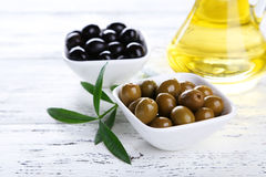 Green and black olives in bowl on a white wooden background Royalty Free Stock Photo