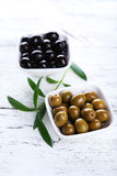 Green and black olives in bowl on the white wooden background Royalty Free Stock Images