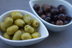 Green and black olives in ceramic pots. Over a grey background Royalty Free Stock Photography