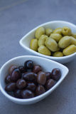 Green and black olives in ceramic pots. Over a grey background Stock Image