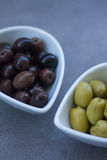 Green and black olives in ceramic pots. Over a grey background Stock Images