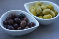 Green and black olives in ceramic pots. Over a grey background Royalty Free Stock Images
