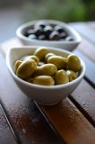 Green and black olives in ceramic pots. On a wooden table Royalty Free Stock Image