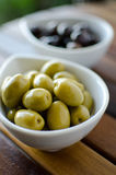 Green and black olives in ceramic pots. On a wooden table Royalty Free Stock Photos