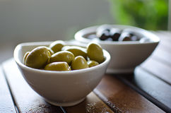 Green and black olives in ceramic pots. On a wooden table Stock Image