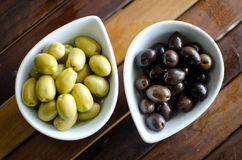 Green and black olives in ceramic pots. On a wooden table Royalty Free Stock Photography