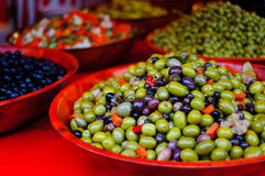 Green and black olives compasition in a red bowl Royalty Free Stock Photo