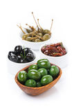 Green and black olives, dried tomatoes and capers, isolated Stock Photography