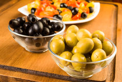 Green and black olives in glass bowl Stock Image