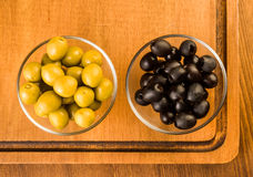 Green and black olives in glass bowl Stock Photos