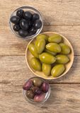The green and black olives. In bowl on wooden background stock photography