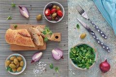 Green and black olives, loaf of fresh multigrain bread, corn sal stock image