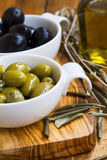 Green and black olives in olive oil on wooden rustic board .Ital Stock Photo