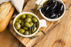 Green and black olives in olive oil on wooden rustic board .Ital Royalty Free Stock Photos