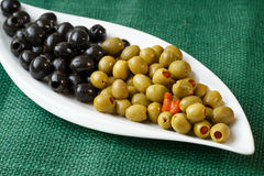 Green and black olives on a plate Stock Photos