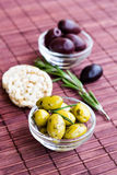 Green and black olives with rice cakes on bamboo napkin Stock Photography