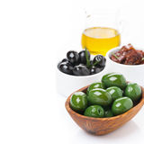 Green and black olives, sun-dried tomatoes and jar with oil Stock Photo