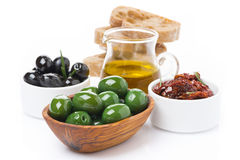 Green and black olives, sun-dried tomatoes, jar with olive oil Royalty Free Stock Photos