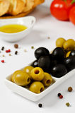 Green and black olives. In white bowl with tomatoes, oil and bread Royalty Free Stock Images
