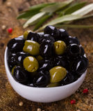 Green and black olives. In a white bowl on wooden background Royalty Free Stock Photos