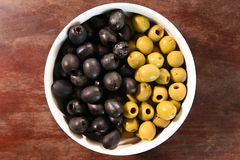 Green and black olives in white bowl Stock Images