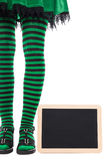 Green and black striped legs from a witch or goblin, slate with Royalty Free Stock Images