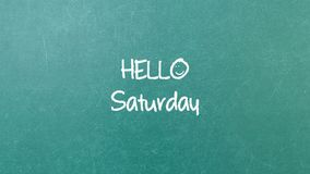 Green blackboard wall texture with a word Hello Saturday. Green blackboard with hand written words note Hello Saturday stock photo