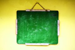 Green balackboard hanging on a yellow wall stock photography